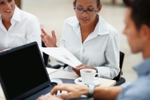 Geschäftsfrau trinkt Kaffee während eines Meetings mit anderen Frauen.